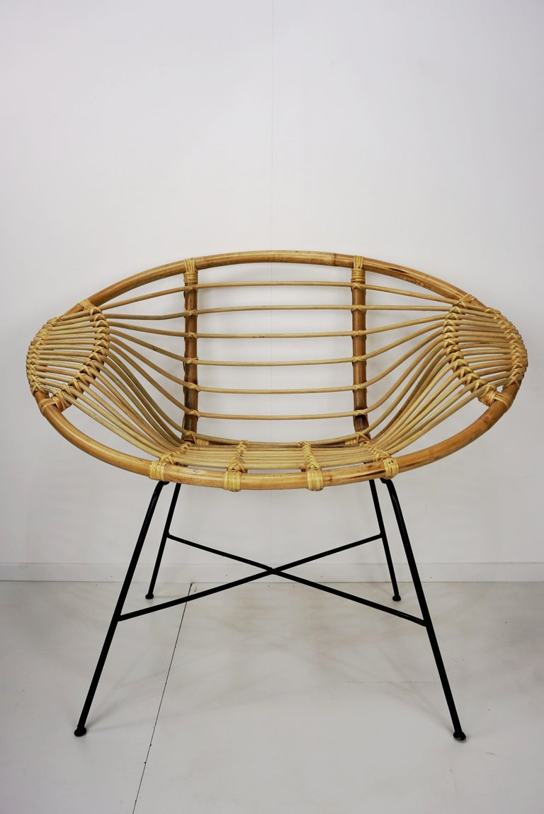 Pair of rattan lounge armchairs at the manner of Janine Abraham and Dirk Jan Rol composed or a braided rattan seat with aerial black metal feet.