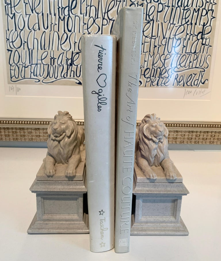 Composition Pair of Reclining Lion Bookends For Sale
