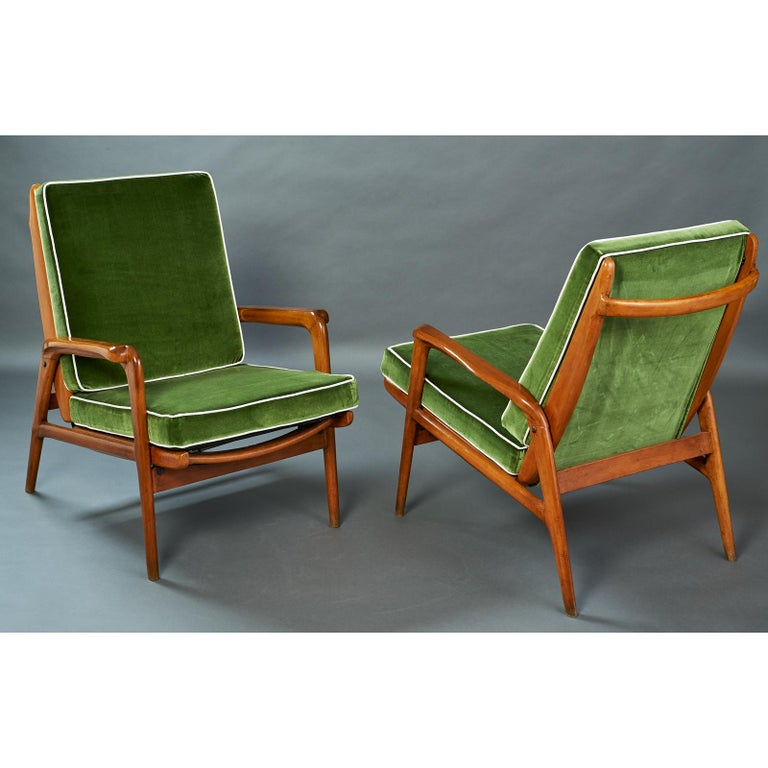 Italy, 1950s Pair of reclining polished wood armchairs with shaped armrests and back grasp Dimensions: 26 W x 34 D x 17 high @ seat, 34 H @ back. Two pair available, similar upholstery but not identical. Sold by the pair
