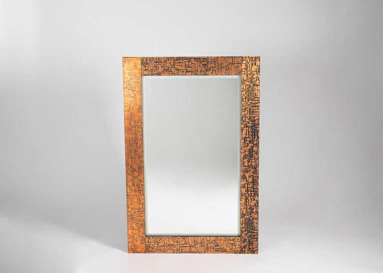 A pair of large rectangular mirrors, framed in wood with a geometric, copper-toned finish in a repeating, crisscrossing geometric.