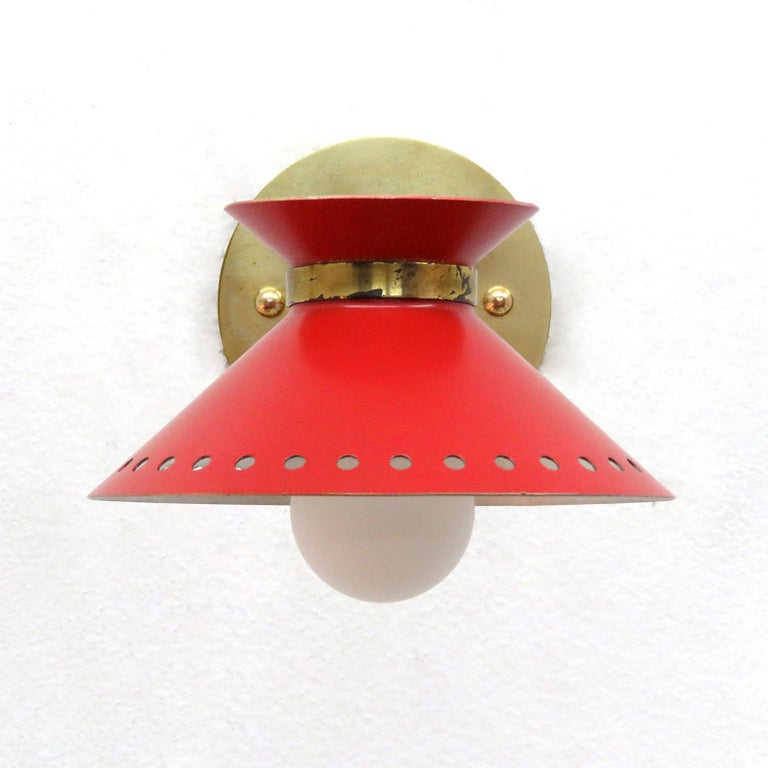 Wonderful pair of red enameled French double cone wall lights by Arlus, with pivoting shades on articulate brass arms, perforated along the bottom edge, wired for US standards, one E12 socket per light, max. wattage 75w, bulbs provided as a one time