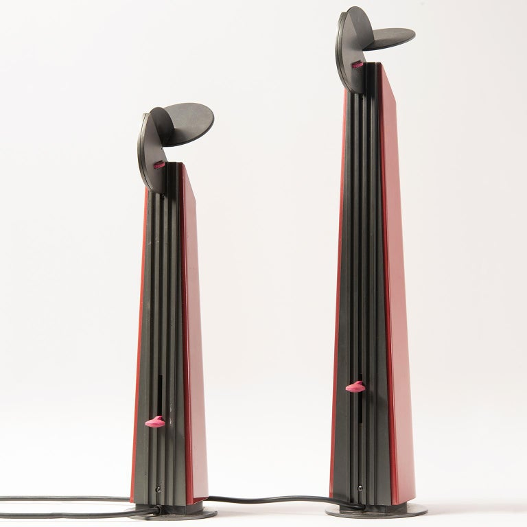Two Gibigiana lamps from Italy designed by Achille Castiglioni for Flos feature dark red bases with black tops, circa 1980s. The Gibigiana lamp casts light in a very specific spot, directing it through a special reflective mechanism. The designer