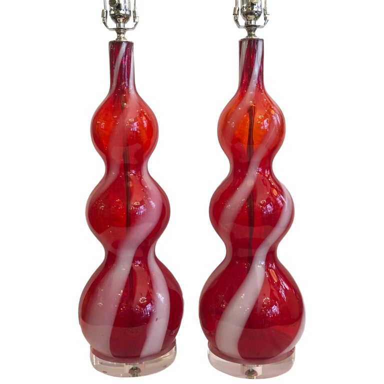Pair of 1960s hand blown Murano lamps in red with white ribbons.  Measurements: Height of body 22.5