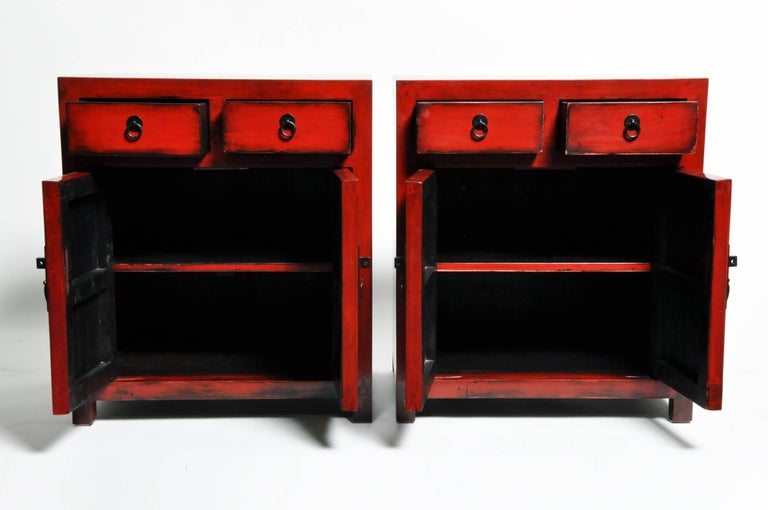 Add a pop of red to any room with this pair of red lacquered side chests from Ningbo, China. Made from reclaimed elm wood and lacquer the pair features mortise and tenon joinery, two drawers, and a shelf each. You can also customize a new one and