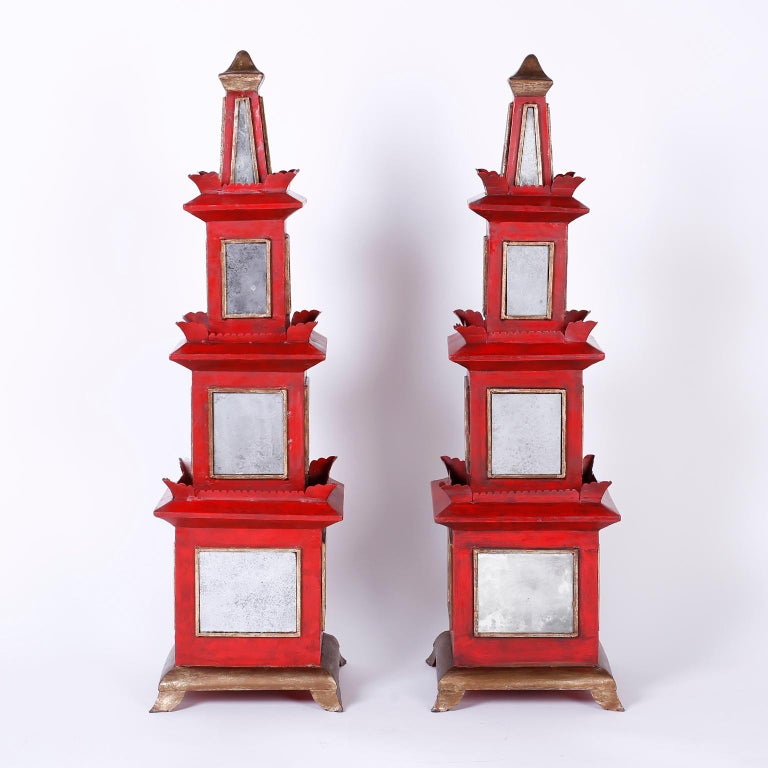 Dramatic pair of midcentury pagodas crafted with wood and metal painted red and decorated with distressed mirrors. The finials, bases, and mirror frames are distressed gold leaf. The large-scale and unusual mixture of materials make these a unique