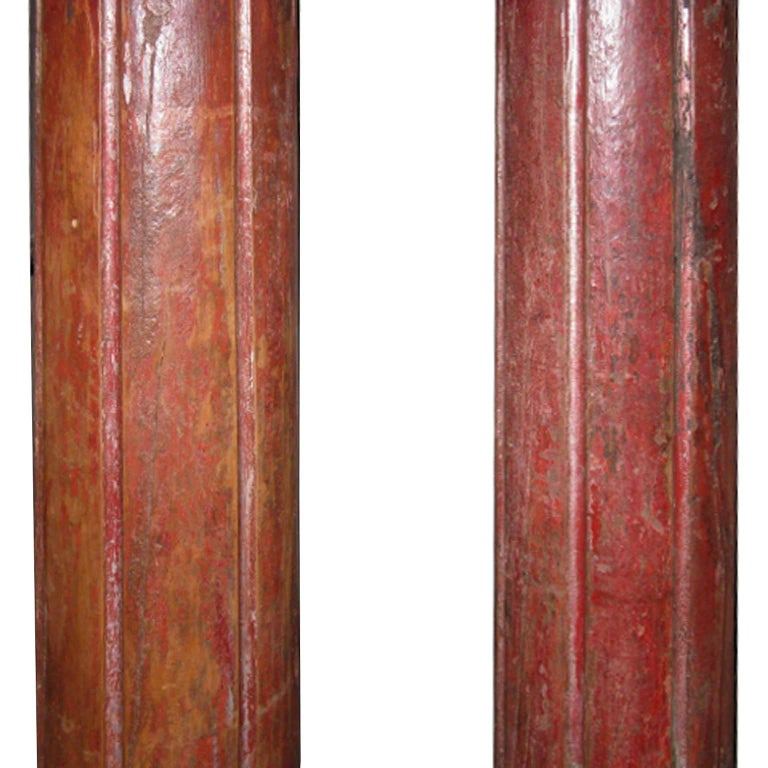 Pair of beautiful hand carved wood columns from a Haveli in Gujarat, India. The columns have carved wood capitals and painted stone bases. Originally used to adorn an entry in a traditional Indian Haveli. Assembly required.