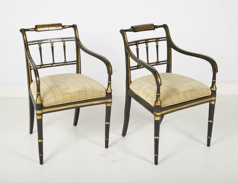 Pair of English Regency painted and gilded armchairs with Greek key motif decoration, turned splat supports and faux bamboo legs. The seats are covered with upholstered cushions.