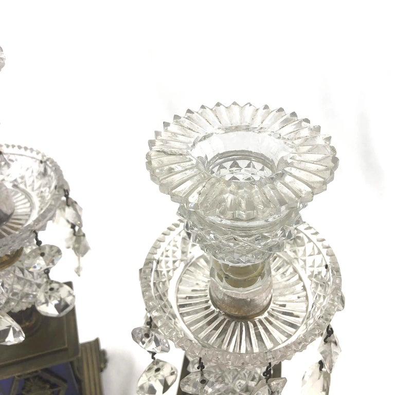Pair of English Regency cast crystal, bronze and cobalt glass candlesticks with palm leaf motifs and a stepped base above antheminion feet.