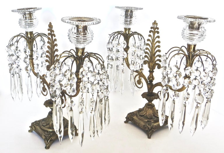 Of British origin, circa 1815, and of Regency design, the bronze platform support, with foliate and flower head ornamented bracket feet, below a collar of leaves, support a central column. The foliate scrolled arms have flower head ornamentation