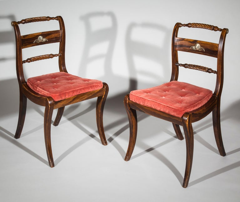 An elegant pair of English early 19th century Regency period Klismos chairs, brass-mounted and faux-bois painted to simulate calamander, with squab cushions,  circa 1820.  Three pairs available in total.  These faux-bois painted and cane-seated