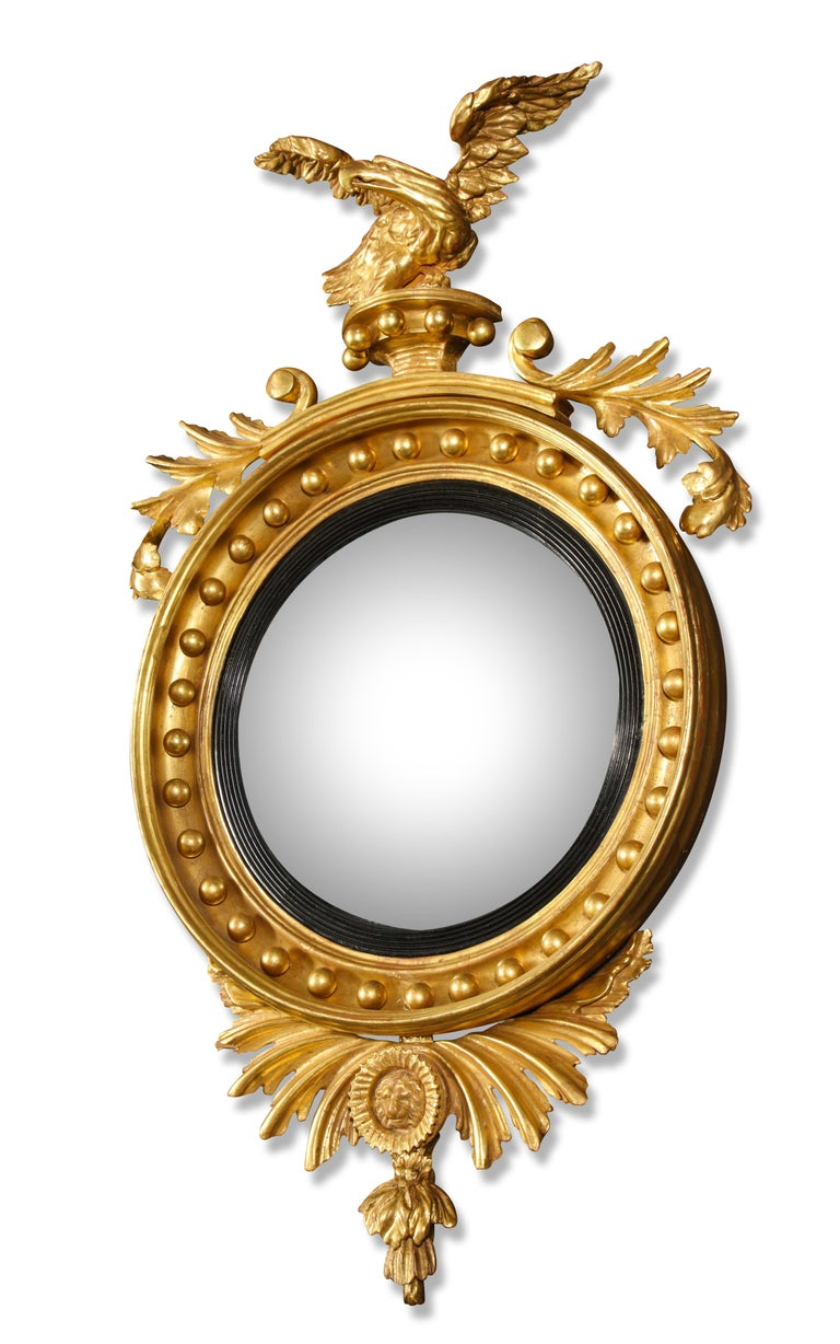 Each mirror having a circular convex glass framed by a ball and bound-reed border; surmounted by an eagle with outswept wings perched on a pedestal flanked by laurel; the undermount with carved acanthus leaves and centered by a classical lion's head.