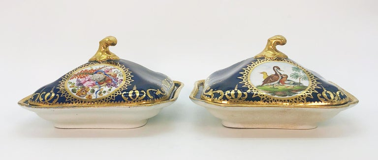 A pair of Coalport cobalt blue square covered vegetable serving dishes decorated with gilded bands of interlocking scrolls and finials. Hand painted panels to dishes and lids, one decorated with waterfowl and game birds and the other with floral