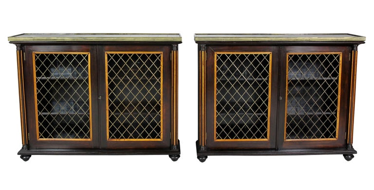 Each with a rectangular marble top comprised of various marble squares and brass banding, the conforming base each with a pair of brass grill doors enclosing shelves flanked by reeded columns. Raised on flattened toupie feet.