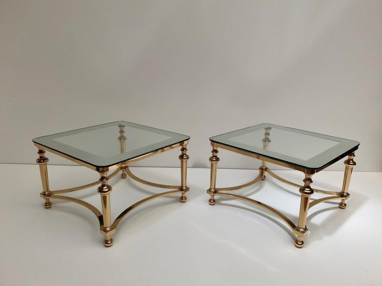 Stunning pair of Hollywood Regency side tables.  The tables are just stunning and elegant, the tops are made of glass on a brass base.   Measurements: 40 cm height x 61 cm width.