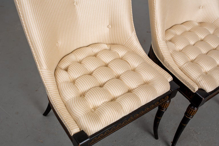 Pair of Regency style, newly upholstered, button-tufted side chairs with black painted frame and carved wood legs with parcel-gilt.