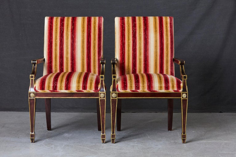 Pair of lovely Regency style fauteuils with painted gilt elements and medallions, upholstered in a colorful red, beige gold striped velvet. Some fading and loss to the velvet and some of the medallions. Seat depth 18 inches, arm rest height 26