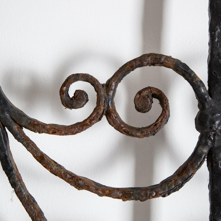 Splendid pair of wrought iron garden gates, circa 1820.  The gates have small modern addition to the side, which allow them to be hung if desired. The door handle has seized over the years and is no longer functioning.  Each gate measures -