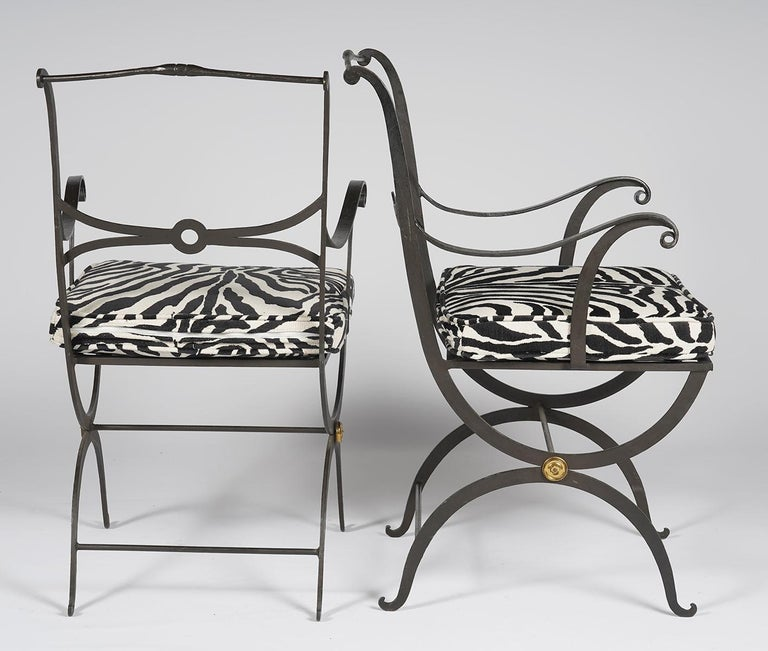 This pair of painted wrought iron stylized Regency armchairs feature Curule style legs centering brass rosettes and elegantly designed backrests. The recent custom made zebra pattern cushions make the combination 'tres chic'. The chairs date to the