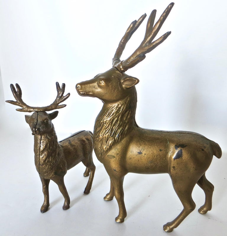These two authentic cast iron antique still banks depict a large reindeer and a smaller one standing nearby. Together, they make a wonderful Christmas or holiday winter display. They are both of American manufacture and were made circa 1910 by the