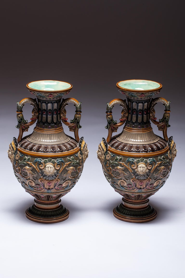 Pair of Copeland Renaissance-style Majolica vases, England, late 19th century, six-panel design carved all-over in low relief with six stylized portrait medallions. Mythological sapphire heads on the sides of vases. The surface of the vases is