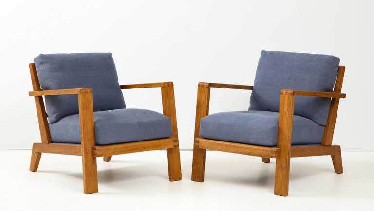 Elegant pair of French Mid-Century Modern lounge or club chairs with angled arms and a grid backrest by René Gabriel, Paris, circa 1945. Newly upholstered in a blue linen fabric.