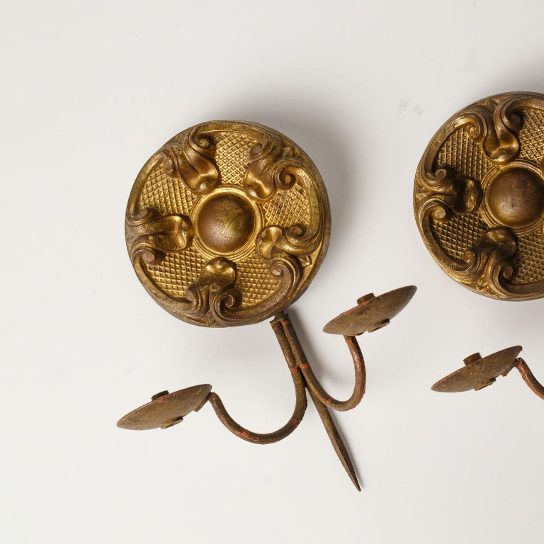 Pair of repousse sconces with two iron arms each. Remnants of gilt decorate surface of the brass repousse. Dating to the mid-late 19th century. Unwired, but can be wired for electricity for an additional cost. Sold together as a pair for $850.