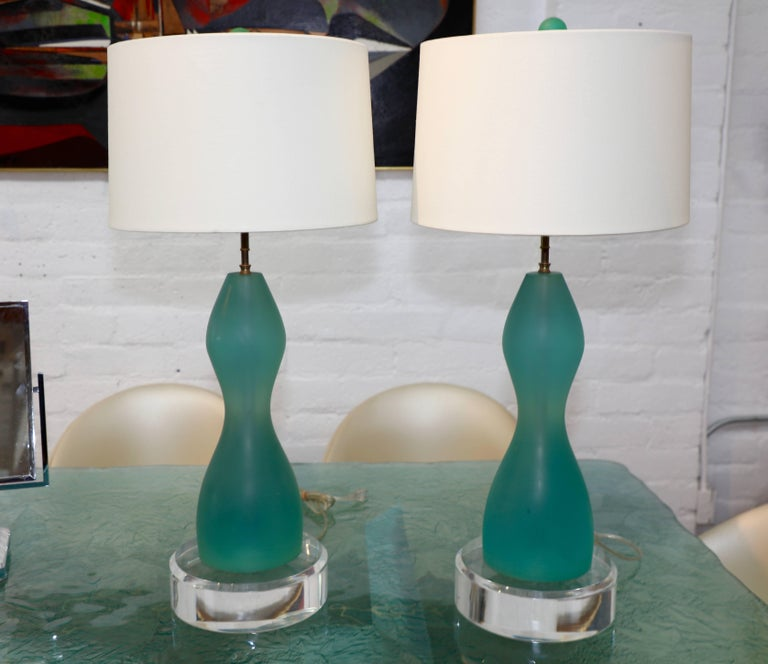A nice pair of resin lamps in a aqua color. They feature Lucite disc bases that are 3 inches thick. These disks are not attached the lamps just sit atop them and are likely later additions. New shades. A nice pair of lamps. Some slight marks and to
