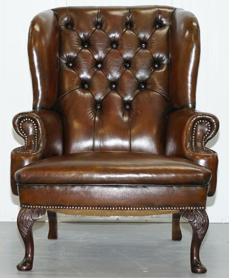 We are delighted to offer for sale this stunning pair of fully restored cigar brown leather Chesterfield wingback armchairs with hand-carved Acanthus leaf cabriolet legs   Please note the delivery fee listed is just a guide, it covers within the