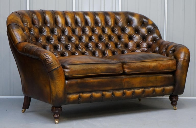 We are delighted to offer for sale this stunning pair of fully restored hand dyed Whisky brown leather Chesterfield two-seat sofas with feather filled cushions  A very good looking and well made pair of sofas, they have feather filled cushions,