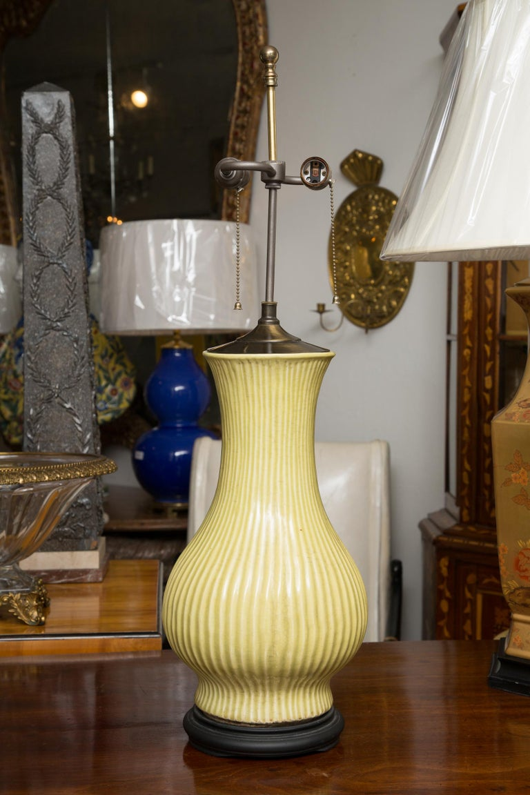 This is a mellow pair of ribbed baluster lamps situated on circular wood bases.