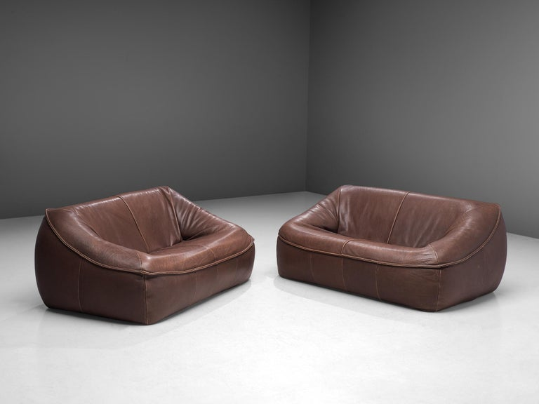 Gerard Van Den Berg for Montis, pair of 'Ringo' settees, buffalo leather, The Netherlands, 1974.  These grand and bulky two-seat 'Ring' sofas are designed by the Dutch designer Gerard Van Den Berg. The sofas arecomfortable and shaped as a large