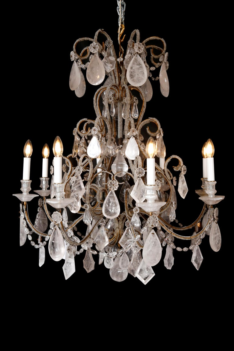 A pair of rock crystal chandeliers with eight arms mounted with drip pans and nozzles. The gilded metal body of curving shapes dressed with fine rock crystal beads in the Genovese style. Profusely hung with unusual pendant shell florette oval beads
