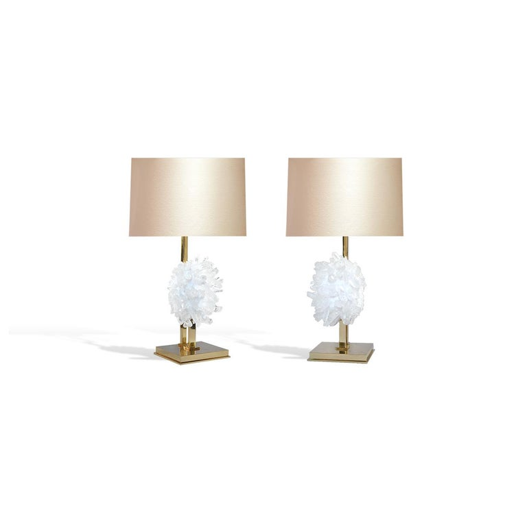 Pair of rock crystal clusters mount as lamps. Polish brass stand. Created by Phoenix. To the top of the rock crystal part: 13 in H each lamp installed two standard sockets lampshade not included.