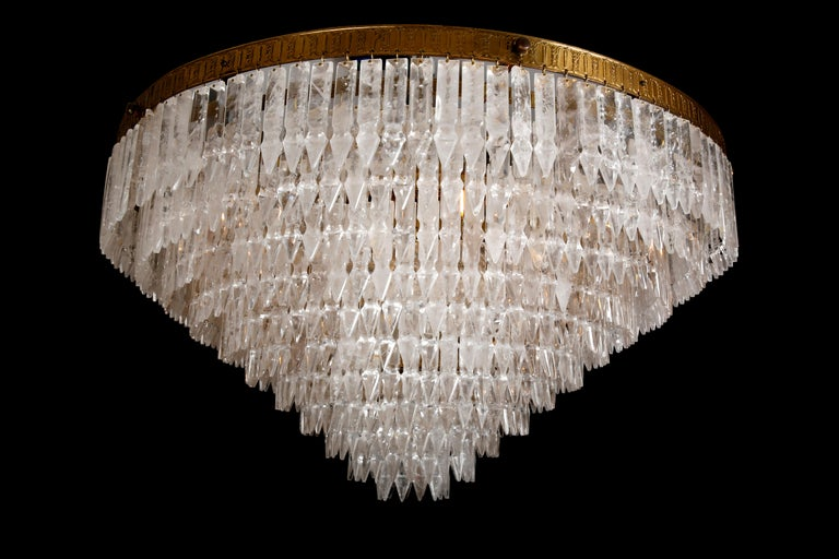 A unique and spectacular pair of rock crystal chandeliers profusely hung with almost 700 individually hand-carved myrzah drops, all mounted on an 11 tiered brass frame. Internally lit by 10 bulbs.