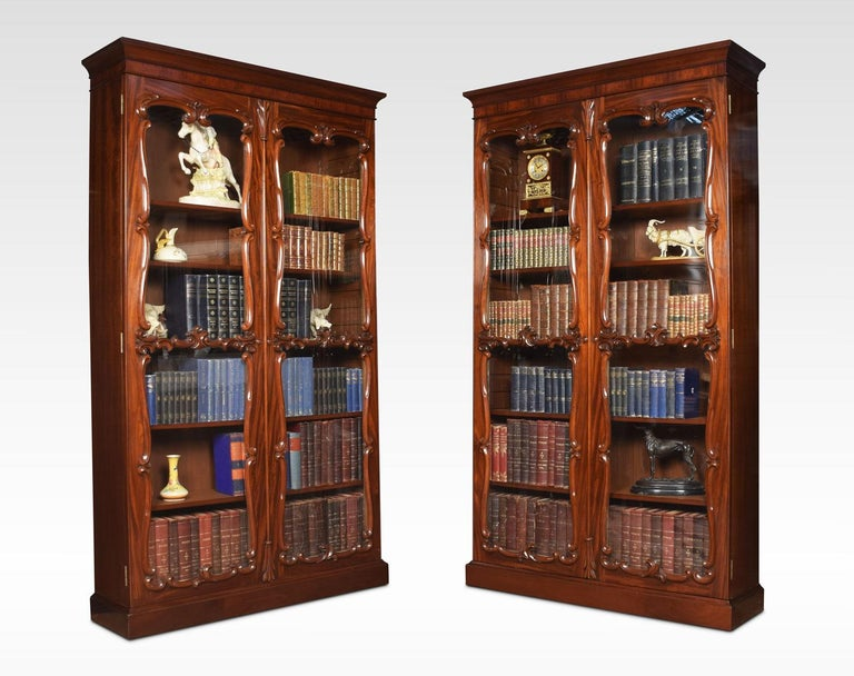 Pair of mahogany bookcases the moulded cornice above a pair of large glazed doors opening to reveal six adjustable shelves all raised up on conforming plinth, adapted from a larger bookcase.