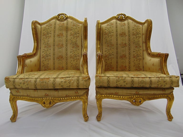 This is a beautiful, opulent pair of vintage wingback gold gilt chairs. These are hand carved and very heavy. They would look absolutely fabulous in a new fabric of your choosing. The measurements are: 28.5'' W x 32''D x 47'' H 26'' armrest height