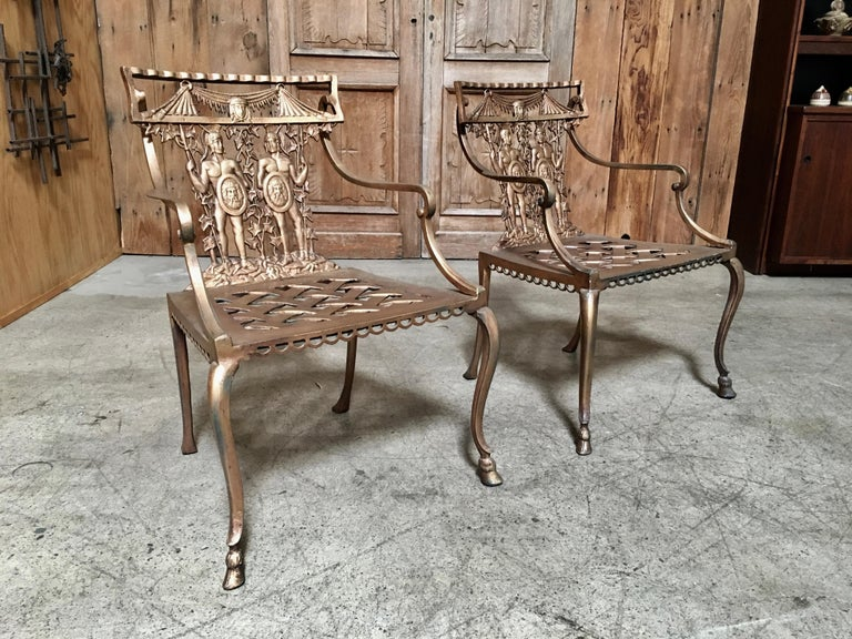 Cast metal patio chairs with naked Roman warriors in a gold bronze finish and basket weave seat made in Mexico.