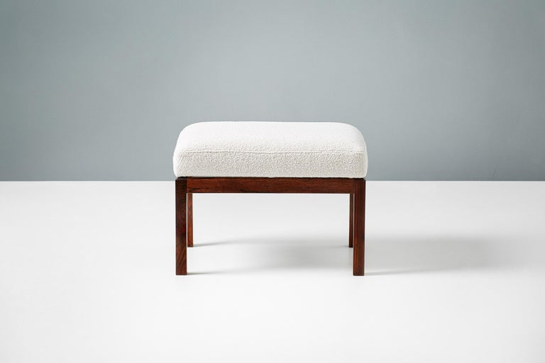 Pair of rectangular ottomans, produced in Denmark in the 1950s. Solid rosewood frames with rectangular seats covered in new off-white luxury bouclé fabric.