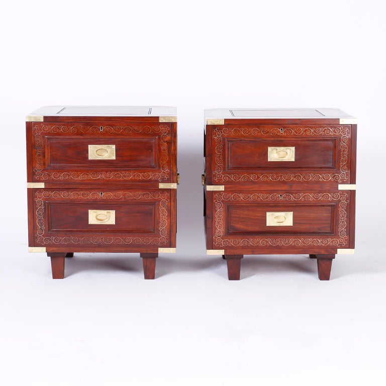 Refined pair of two-drawer Anglo Indian stands crafted in well grained rosewood with Campaign brass hardware, finished on all four sides, delicate brass string inlaid in floral design and tapered legs. Signed in a drawer M.Hayat & Bros LTD.
