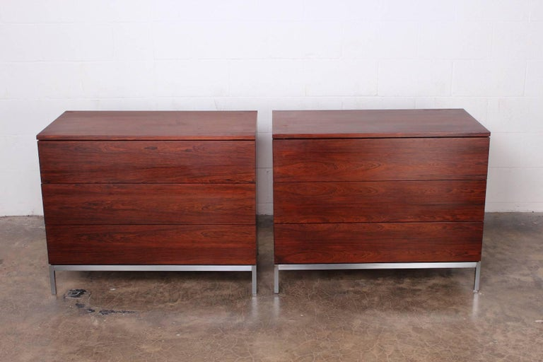 A pair of matching rosewood three-drawer dressers with brushed chrome bases. Designed by Florence Knoll for Knoll.