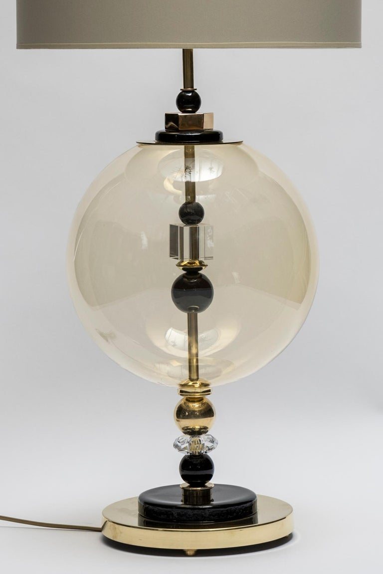 Pair of table lamps made of brass with black Murano glass pieces and a large globe as a centrepiece.