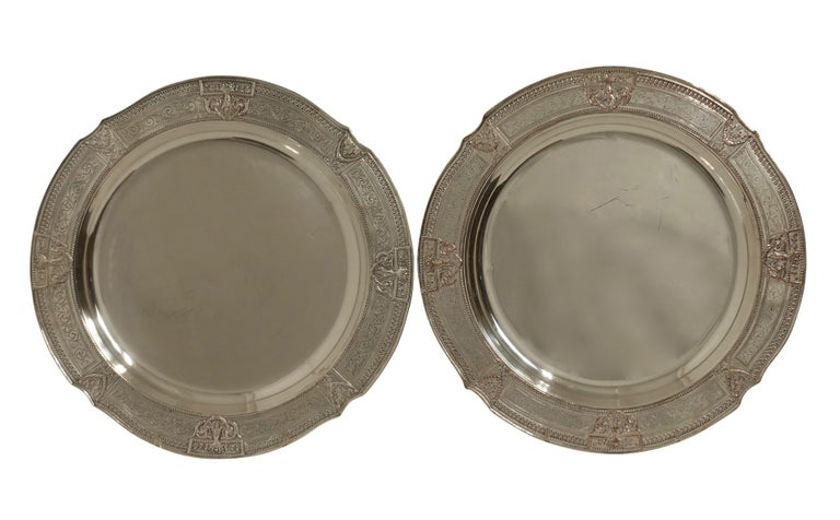 Pair of round neoclassical style silver plate on copper trays with flanking medallions of urns with swags and border of scrolling acanthus leaves. Both have impressed marks on the underside for E. G. Webster of New York, circa 1900.