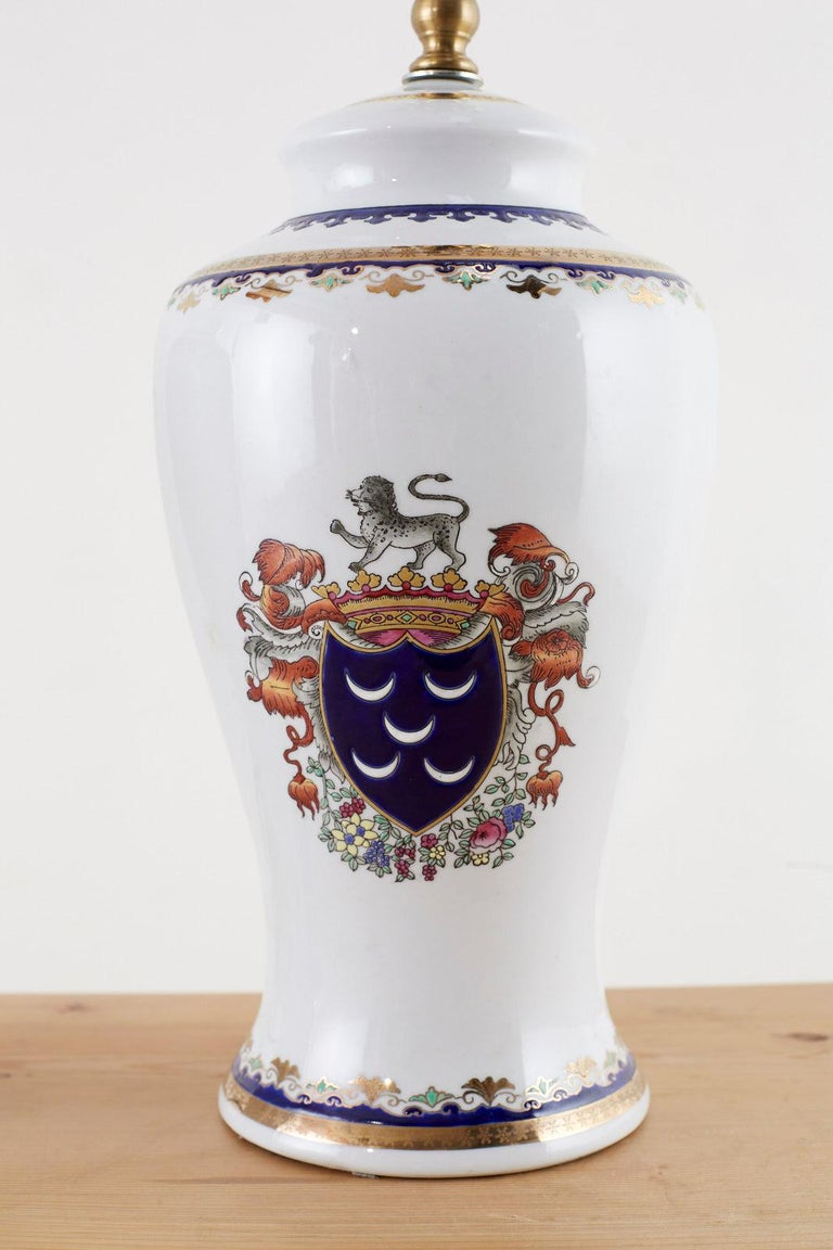 Stately pair of porcelain jar or vase table lamps featuring British style coat of arms motifs on each side. Each side depicts a royal shield in Lapis surmounted by a gold crown with a lion on top. Beautifully decorated with gilt highlights and