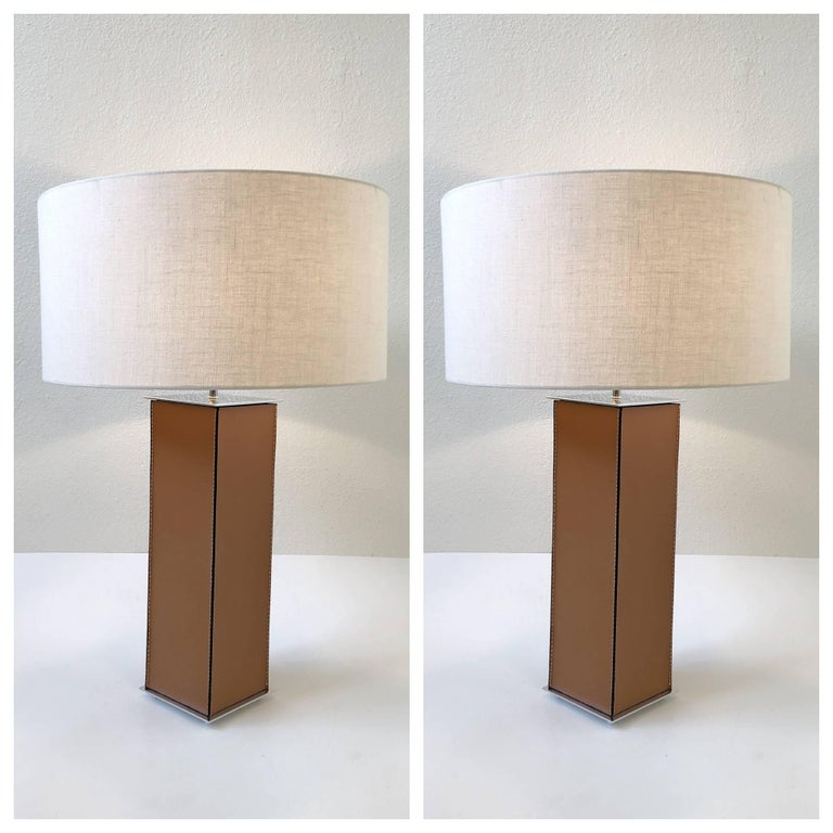 """A glamorous pair of saddle stitch leather table lamps from the 1970s by Laurel Lamps. The lamps have been newly rewired and new linen shades.  Dimensions: 30.5"""" high, 20"""" diameter. Base is 6"""" by 6""""."""