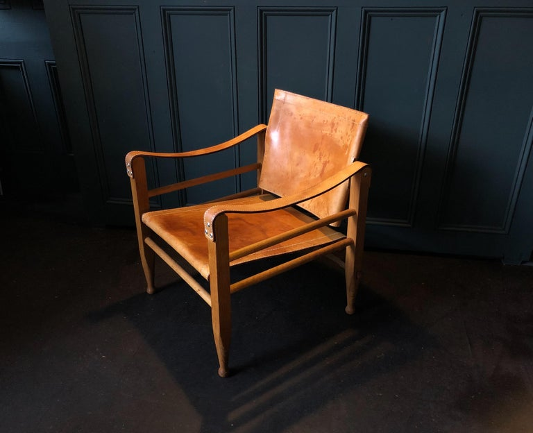 Scandinavian midcentury classic. Matching pair of safari chairs. Børge Mogensen design for Aage Bruun and Son with a rather rare matching table. Beautifully aged Cognac saddle leather upholstery on a European white oak frame. Produced by Aage Bruun