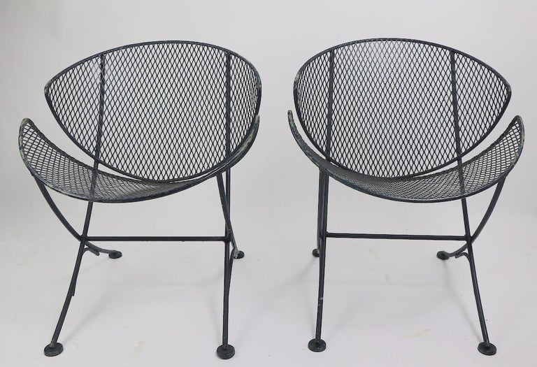 Pair of wrought iron and metal mesh lounge designed by Maurizio Tempestini and manufactured by Salterini. Wrought iron frames with metal mesh seats and backs. Both chairs are in very good original condition, showing only cosmetic wear to the paint