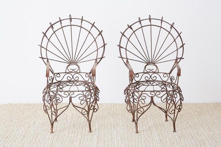 Phenomenal pair of miniature wrought iron peacock chairs designed by John Salterini. This diminutive set of doll size chairs were made as sales samples featuring intricate iron work. Impressive attention to detail with excellent joinery and iconic