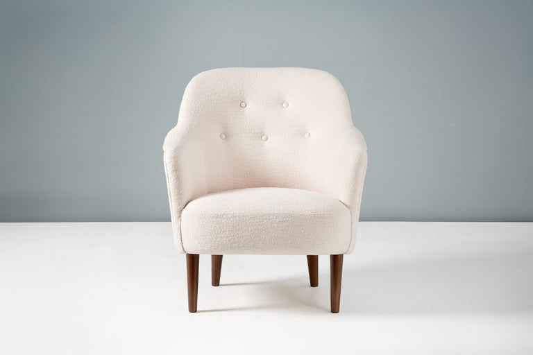 A pair of armchairs designed by Carl Malmsten in 1956 and produced by AB Record in Sweden. This pair have been reupholstered in Chase Erwin 'Laine Snow', a luxurious pure wool fabric. The legs are stained beech.