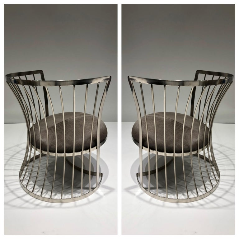 """A glamorous pair of satin nickel lounge chairs, design in the 1960s by Russell Woodard. The chairs have been newly replated and the seats recovered in a gray cowhide. Dimensions: 26.5"""" high 25"""" diameter 15"""" seat."""