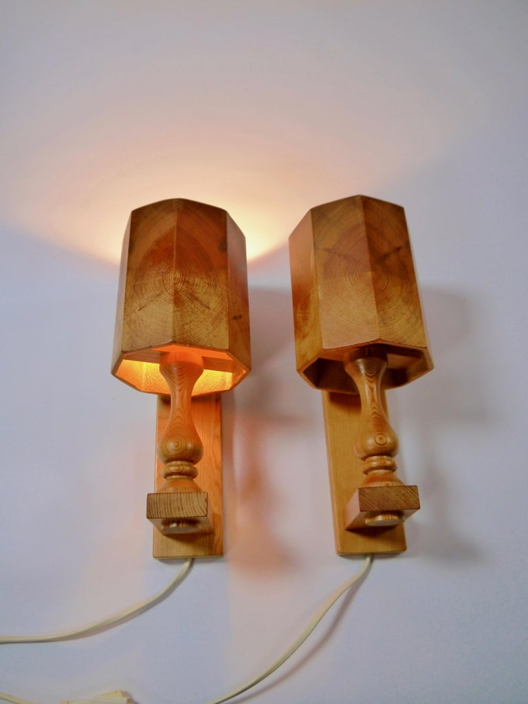 A pair of pinewood wall sconces fabricated in Sweden, 1970s. All solid pinewood, base and shade.